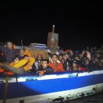 Migrants onboard a drifting overcrowded wooden boat react during a rescue operation by the Spanish NGO Proactiva Open Arms, north of the Libyan city of Sabratha in central Mediterranean Sea