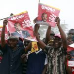 Supporters of Kenya's Deputy PM and presidential candidate Kenyatta hold his posters during a campaign rally in the Rift Valley town of Suswa